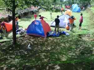 Para siswa sedang mendirikan tenda
